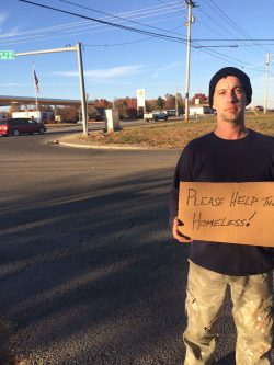 "Ron Rohrbach,stands at an intersection with a sign asking passing motorists to ""help the homeless."""